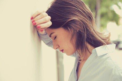 En kvinne som lener hodet til en vegg og ser lei seg ut.