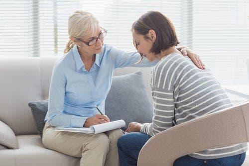 En kvinne som sitter med en kvinnelig psykolog i en terapitime.