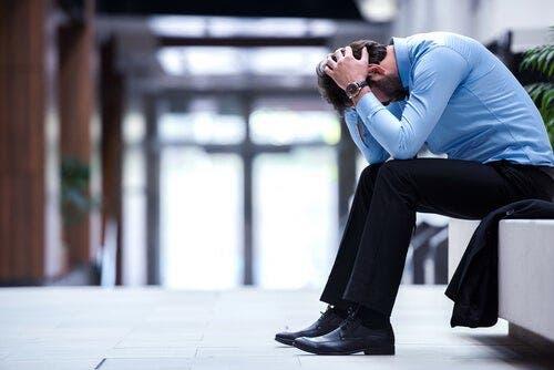 En stresset mann sitter med hodet bøyd i fanget.