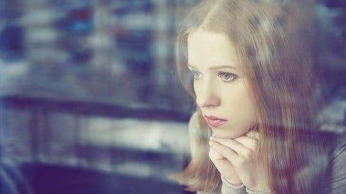 En trist kvinne som ser ut av vinduet.