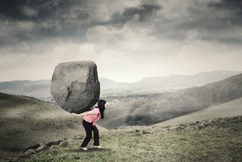 En kvinne vandrer i et fjelllandskap med en stor sten på ryggen.