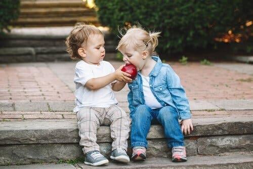 To barn som deler et eple.