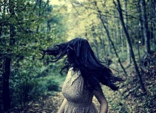 En kvinne i skogen som ser bak seg