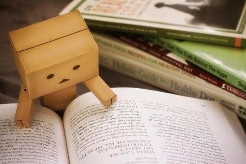 En figur av papp som leser en bok
