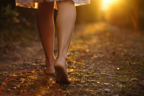 En kvinne som går i solnedgang.