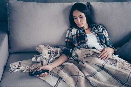 En kvinne som sover på sofaen.