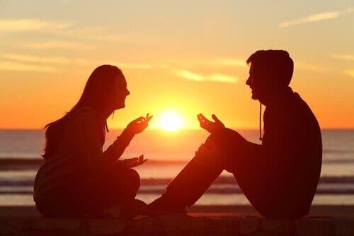 To mennesker som snakker sammen ved havet