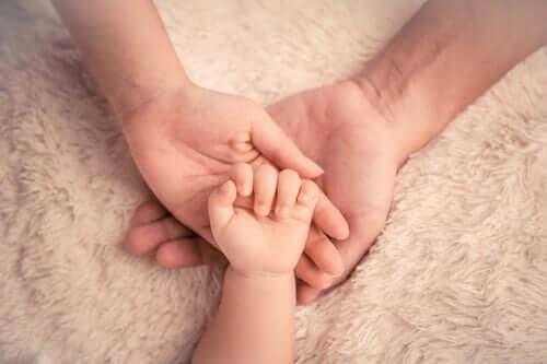 En babyhånd i voksnes hender