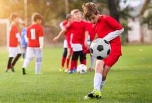 En gutt i et ungdomsfotballag som sparker en ball.