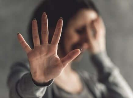 En kvinne som forsvarer seg mot seksuell vold med hånden.