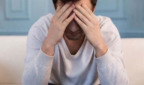 En mann som gnir pannen i frustrasjon.
