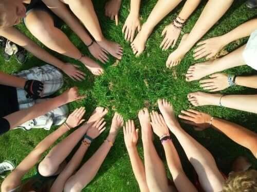 En sirkel laget av menneskers hender og føtter.