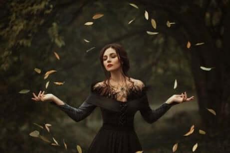 En kvinne med åpne armer lager en sirkel av blader.