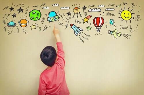 Et barn som peker på tegninger på en vegg