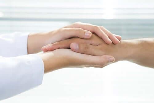 En lege som holder en persons hånd