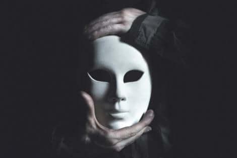 En person som holder en hvit porselenmaske.