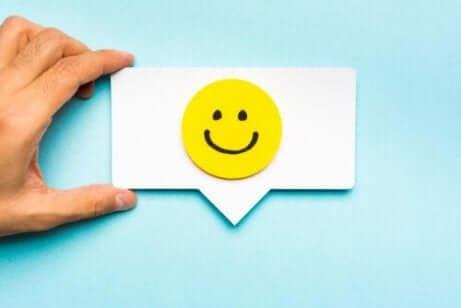 Et visittkort med et smilefjes på, som representerer emosjonell merkevarebygging.