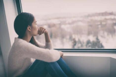 En deprimert kvinne som ser ut av vinduet på en overskyet dag.