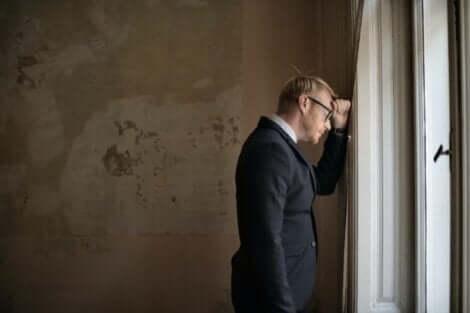En fyr ved et vindu som prøver å godta feilene sine.