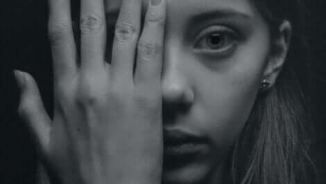En kvinne som dekker ansiktet sitt med hånden.
