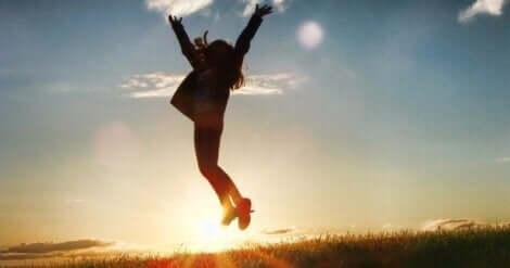 En kvinne som hopper foran solen.