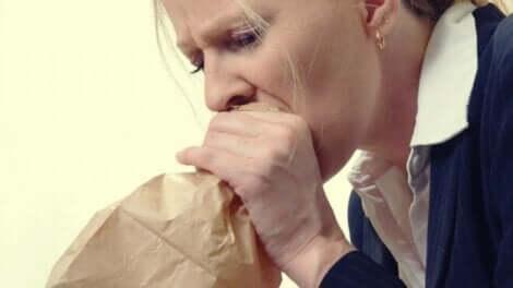 En kvinne som hyperventilerer mens hun puster i en pose.