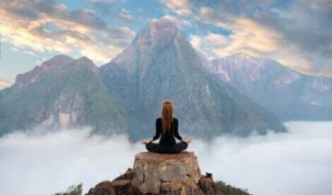 En kvinne som mediterer på fjellet.