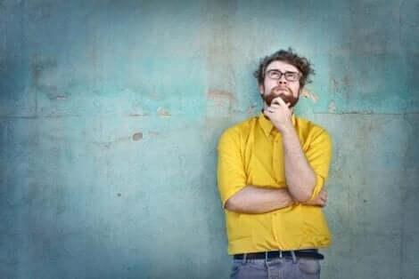 En mann som tenker mens han lener seg inntil en blå vegg.