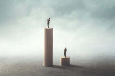 To personer som står på stolper i forskjellige høyder.