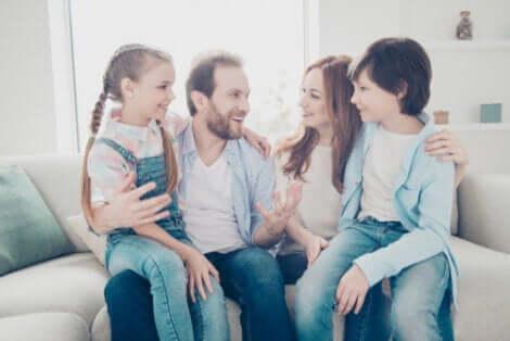 Et foreldrepar med to barn på en sofa