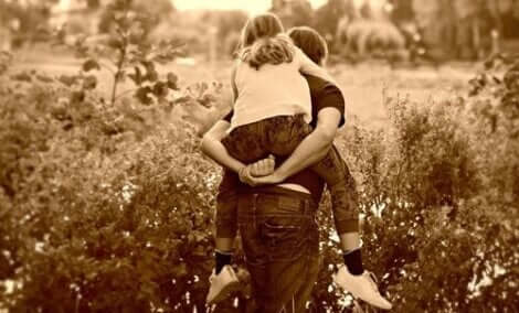 En jente som sitter på ryggen til faren sin