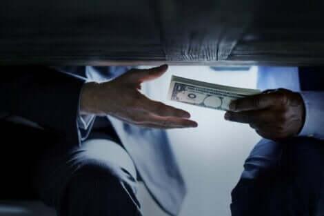 En korrupt person som gir penger under bordet.