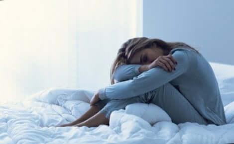 En kvinne som sitter i sengen.