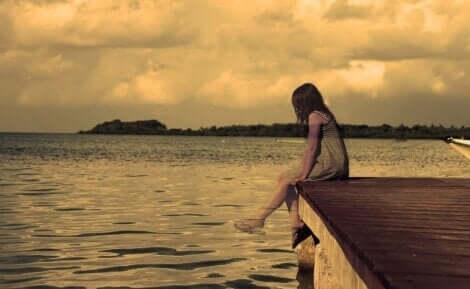 En jente som sitter på en brygge