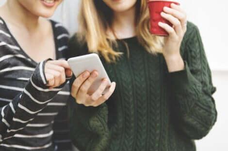 To jenter som ser på en mobiltelefon
