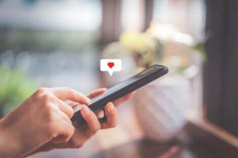 En mobiltelefon med en snakkeboble med et hjerte