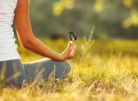 En kvinne som mediterer med en sommerfugl på fingeren