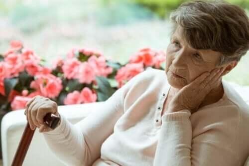 En gammel kvinne med Alzheimers som sitter og ser ut i luften.