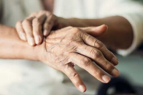 En gammel kvinne som lider av skjelvende hender.