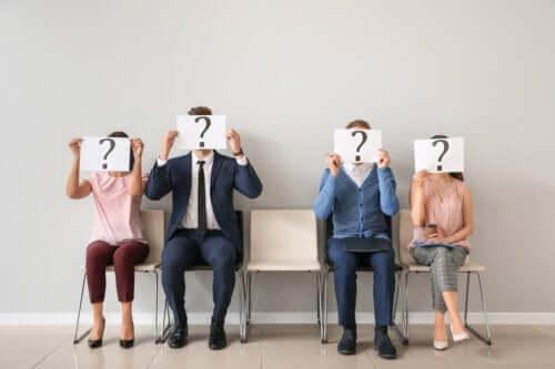 En gruppe mennesker som holder et skilt med et spørsmålstegn foran ansiktet.