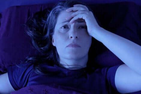 En kvinne i sengen med hodepine.