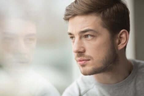 En mann som ser ut av et vindu.