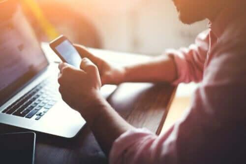 En mann som sjekker ut sine sosiale medieplattformer på smarttelefonen sin.