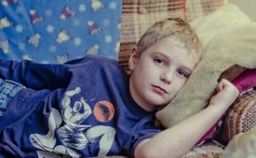En trist gutt som ligger på sofaen.