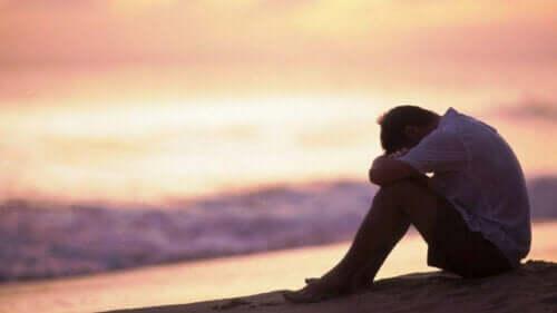 En trist mann som sitter ved stranden og tenker på ytre følelsesregulering.