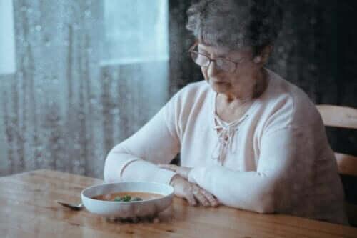 En eldre kvinne som er lei seg og ser på en tallerken med mat.