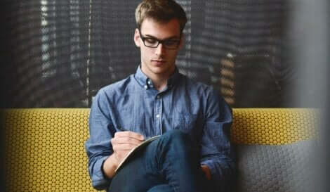En fyr som sitter på sofaen med briller.