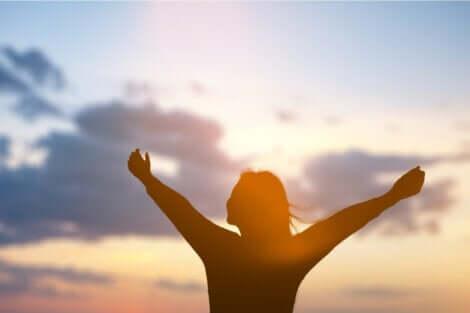 En kvinne med åpne armer som tenker på om bevissthet er et produkt av hjernen.