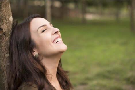 En lykkelig kvinne som lener mot på et tre.