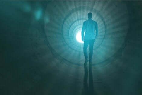 En mann som går mot lyset i enden av tunnelen.